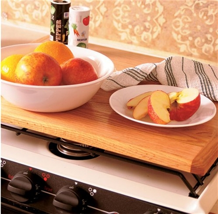 What keeps the Camco oak universal stove top oak board from sliding around?